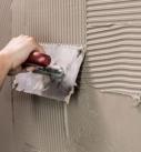 1. Aufspachteln Zunächst wird eine dünne Kontaktschicht ganzflächig auf die Wand gespachtelt. Darauf dann genügend Mörtel auftragen und sofort mit der Zahntraufel (Zahnung 6 – 8 mm je nach Untergrund) gleichmäßig auf-kämmen. Die Holzpaneele sollte man auf der Rückseite leicht mit Wasser anfeuchten damit der Kleber darauf besser hält. Foto: Uzin Utz