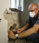 Hohl liegender und damit nicht mehr tragfähiger Altputz muss mit Hammer und Meißel bis auf das nackte Mauerwerk abgebrochen werden. Bei Abbrucharbeiten Staubschutzmaske tragen! Foto: Thomas Schwarzmann